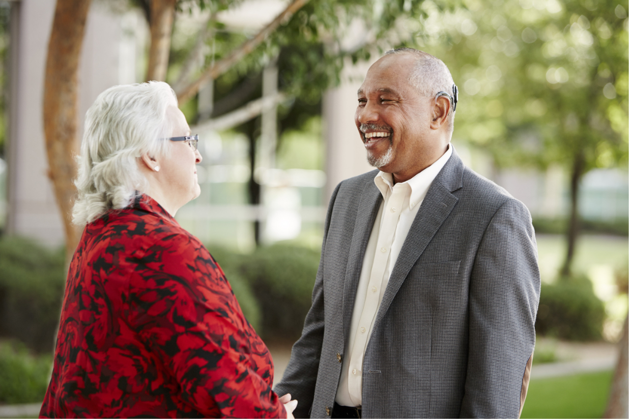 Man smiling and talking to a lady
